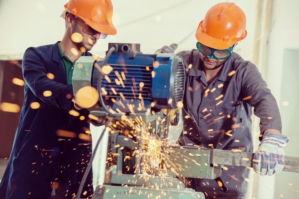 A photo of two factory workers working on heavy machinery