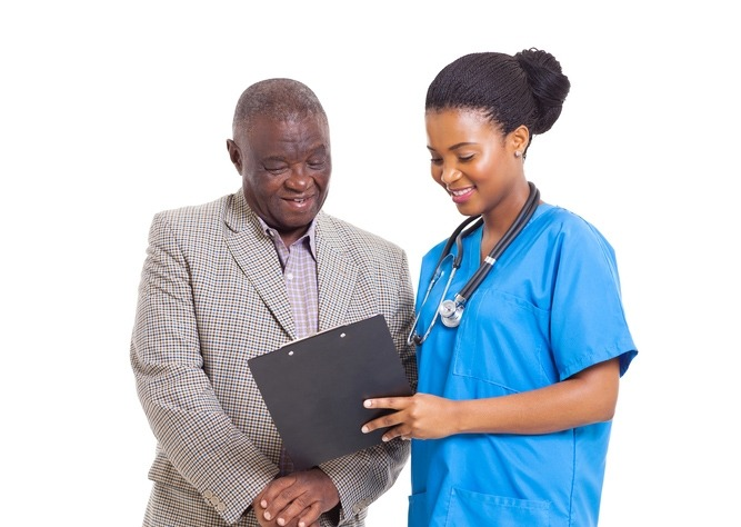 A young female healthcare worker discusses information with an elderly man.