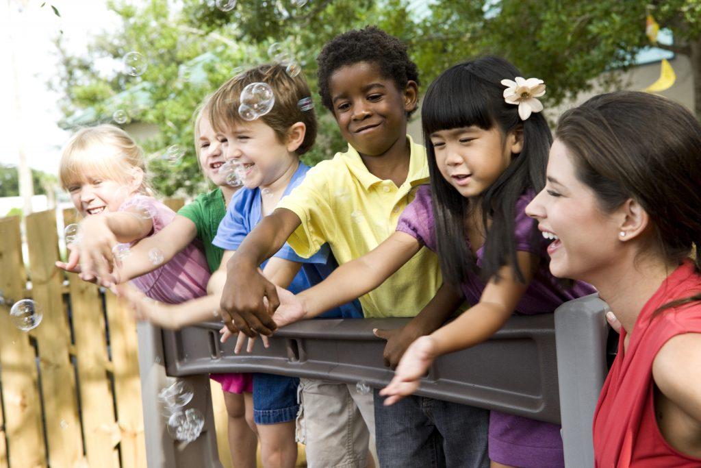 5 preschool children playing on playground with teacher